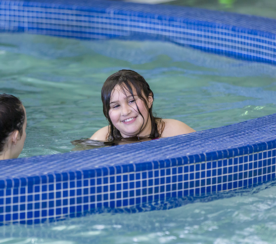 Girl swimming in the indoor activity pool in an adaptive program