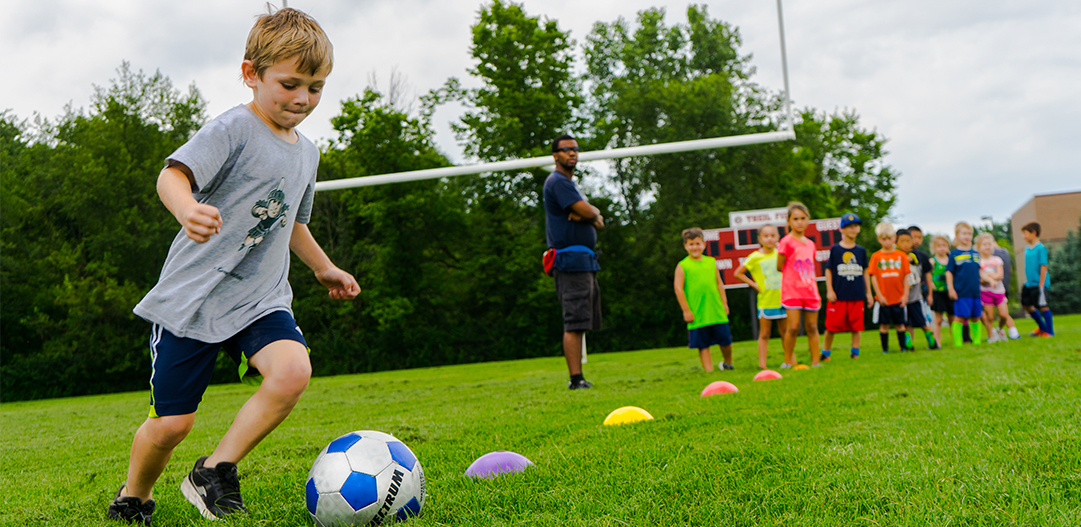 Kid playing soccer at sports summer camp