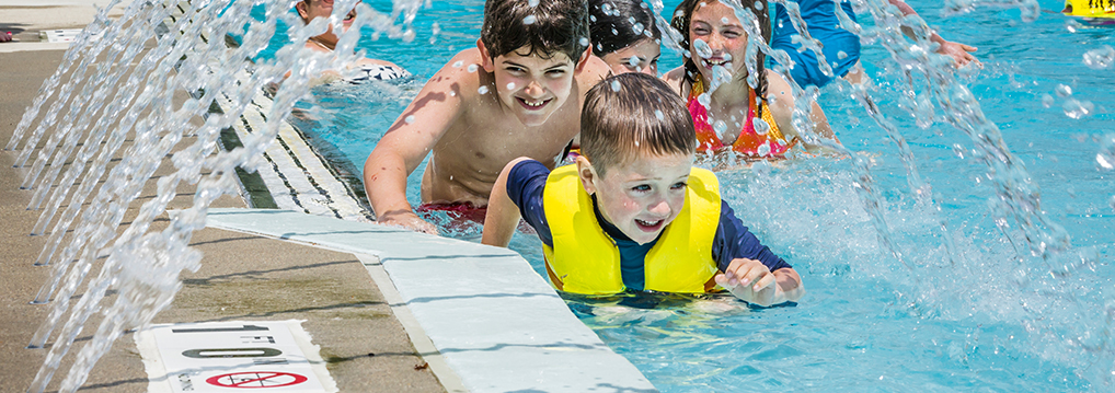 kids in a pool with splashing water