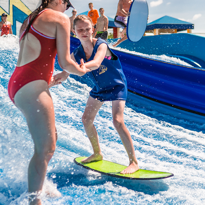 young girl being helped on the flowrider