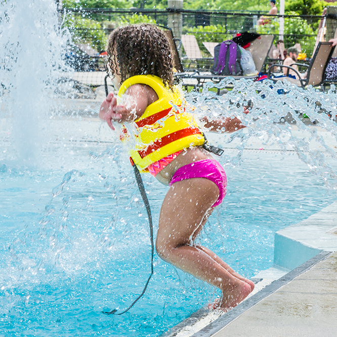 young girl jumping into a pool