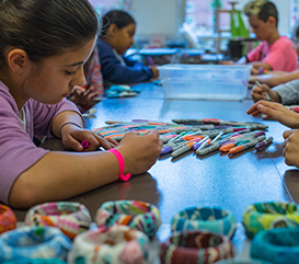 Girl making jewelry in an Adventures in Art summer camp