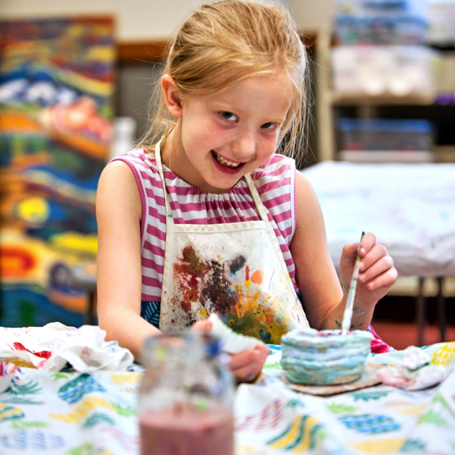 Girl painting in an adventures in art summer camp