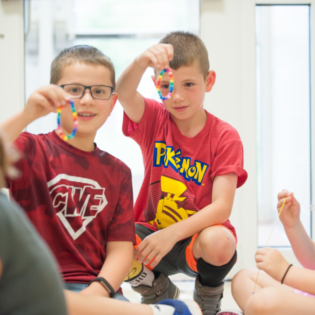 Kids building necklaces in an adventures in art summer camp