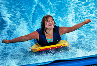 A smiling girl on the FlowRider at the Waterpark, where lifeguards offer surf instruction