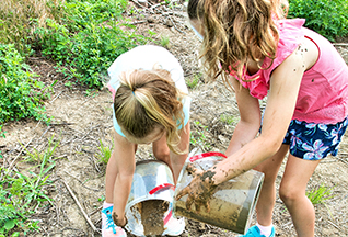 girl teaching another girl how to work with plants and soil in nature camp, learning leadership skills by mentoring