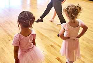 Ballet instructor mentoring two girls at a ballet class