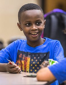 Boy playing cards at the Extended School Enrichment (ESE) program