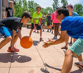 Kids playing basketball at a summer camp
