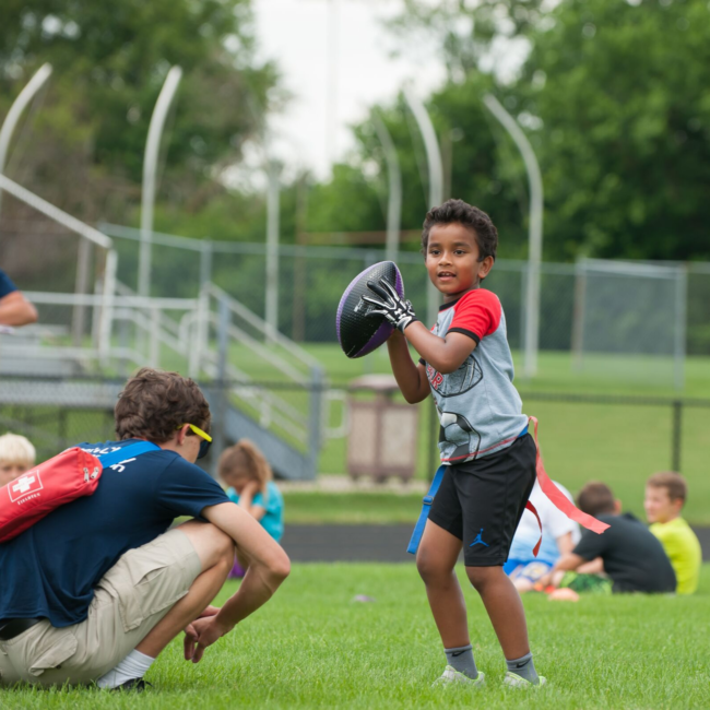 Kids playing flag football at a move to improve summer camp