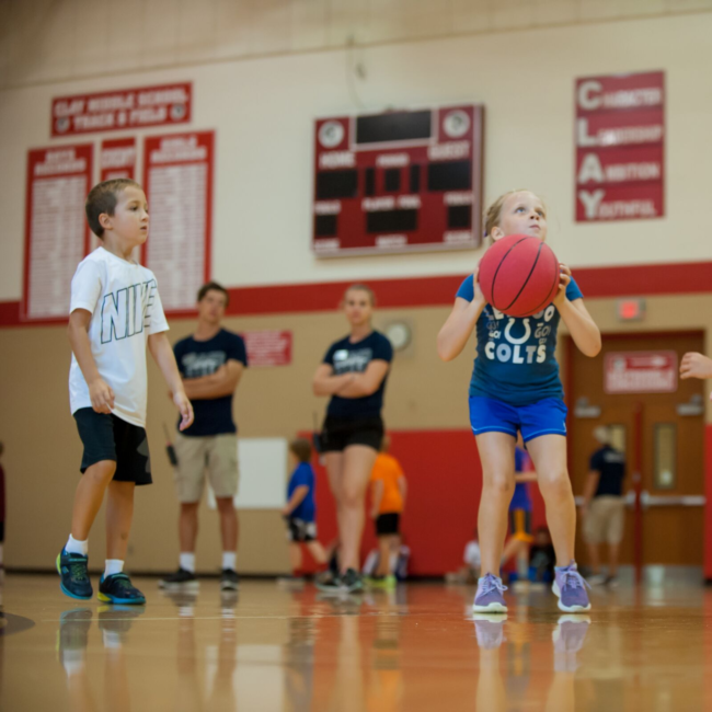 Kids playing basketball at a move to improve summer camp