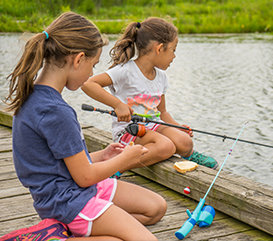 Girls fishing in an outdoor explorers summer camp