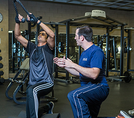 personal trainer coaching someone on a weight machine