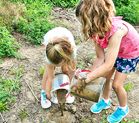 2 girls pouring mud in a half day summer camp