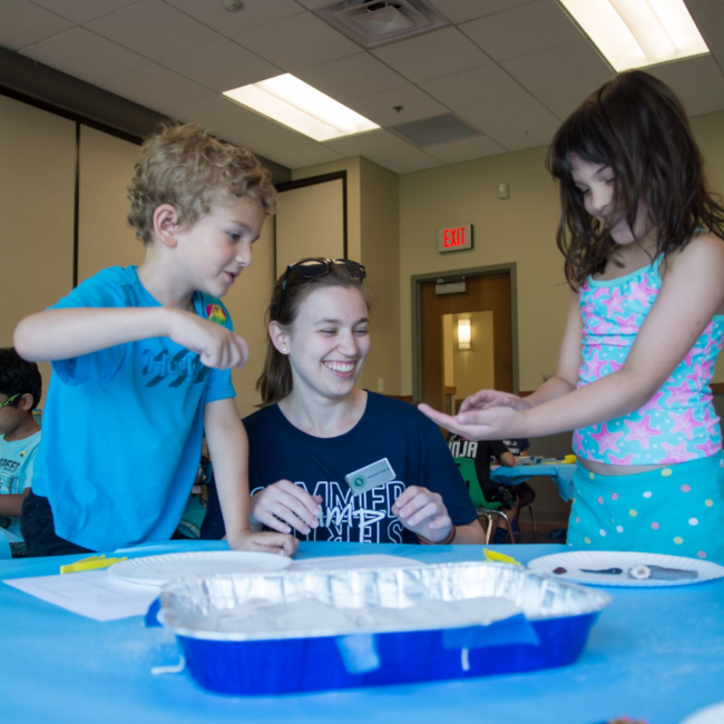 Camp counselor teaching kids science at a science of summer camp