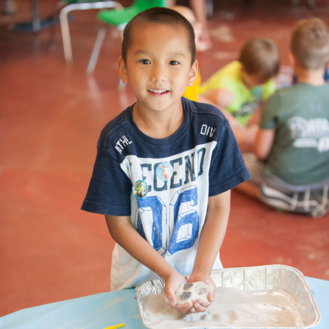 Kid smiling at a science of summer camp
