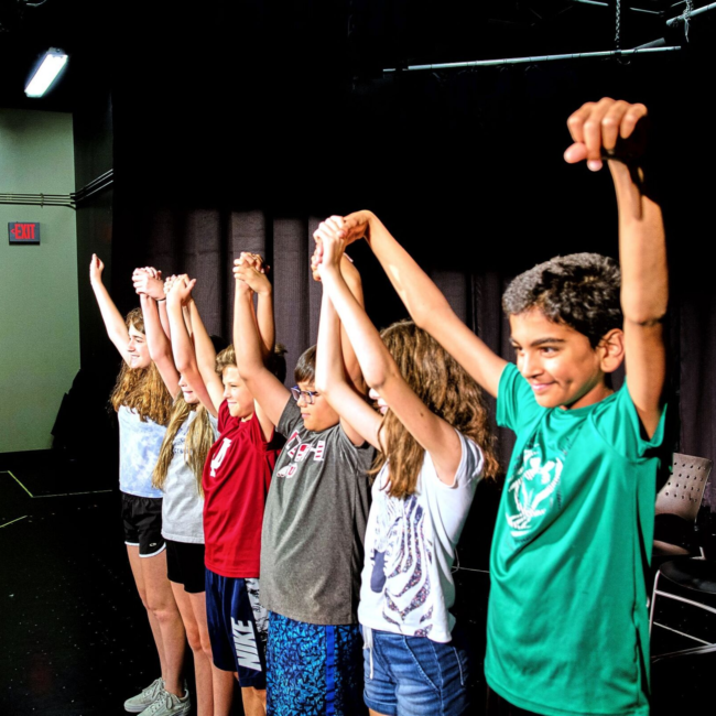 Kids bowing on stage at a success on stage acting summer camp