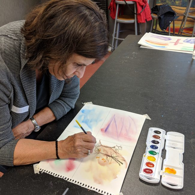 Woman painting in a senior program