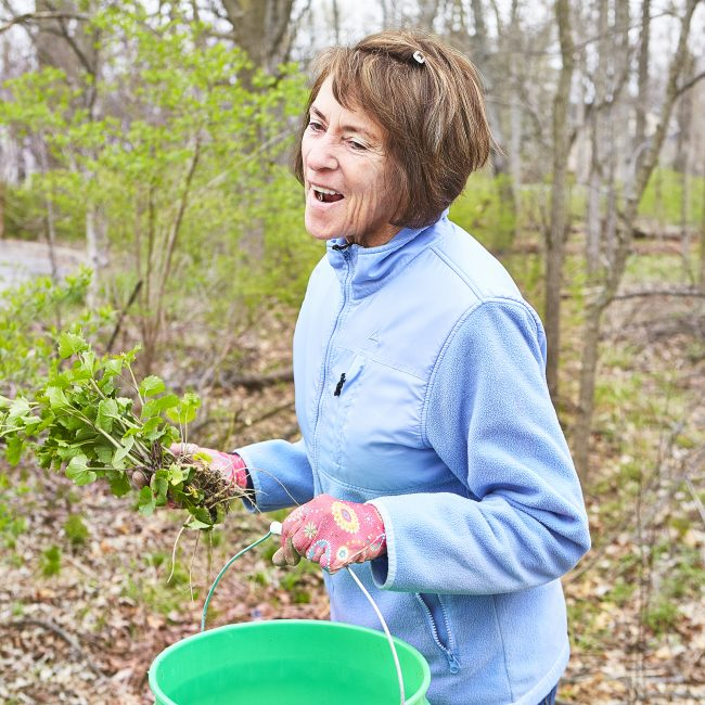 Woman smiling and cleaning our parks