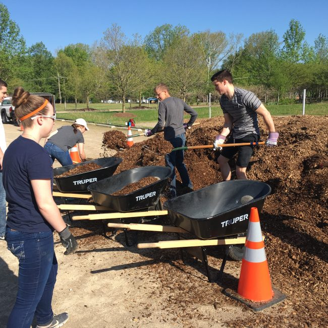 Volunteers shoveling mulch at our park