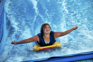 Girl smiling on a surfboard while on the FlowRider in our adaptive program