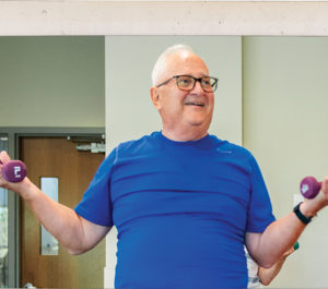 Hank Levandowski lifting weights during SilverSneakers group fitness class at the MCC