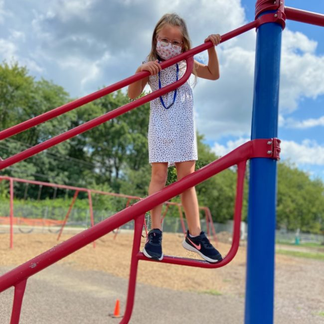 Girl on the playground with a mask on