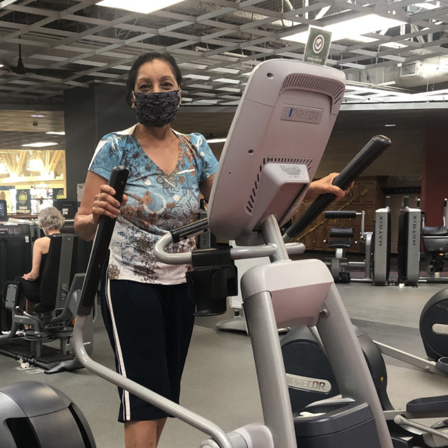 Member on an elliptical wearing a mask