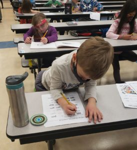 Kid writing at a desk