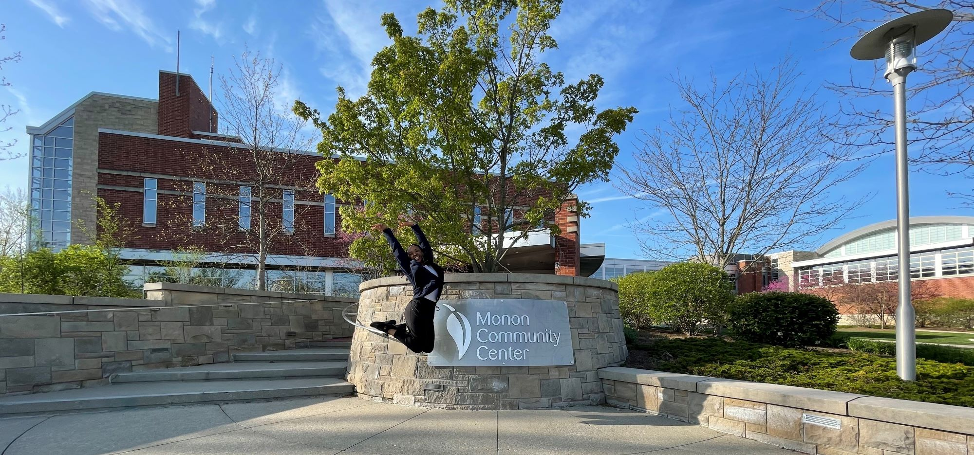Breanna jumping in front of the Monon Community Center